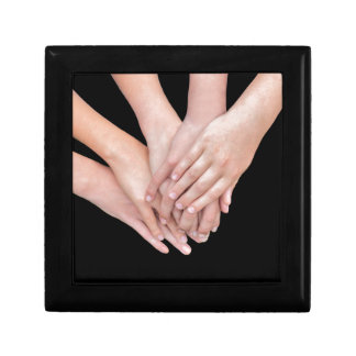 Arms of girls with hands over each other gift box