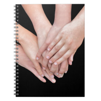 Arms of girls with hands over each other note books