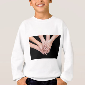 Arms of girls with hands over each other sweatshirt