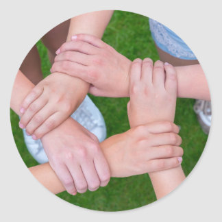 Arms with hands of children holding together classic round sticker