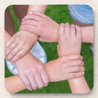 Arms with hands of children holding together coaster