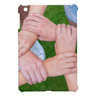 Arms with hands of children holding together iPad mini cover