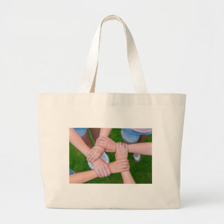 Arms with hands of children holding together large tote bag