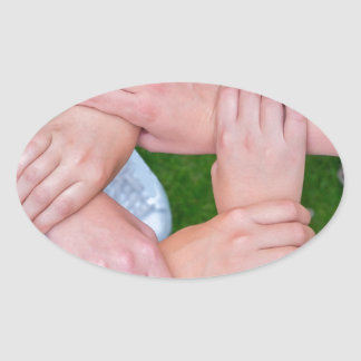 Arms with hands of children holding together oval sticker