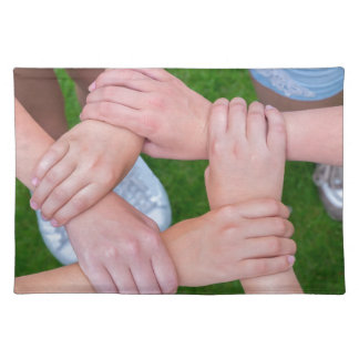 Arms with hands of children holding together place mat