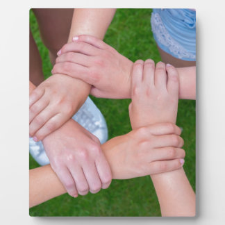 Arms with hands of children holding together plaque