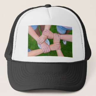 Arms with hands of children holding together trucker hat