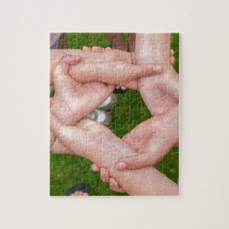 Arms with hands of girls holding each other jigsaw puzzle