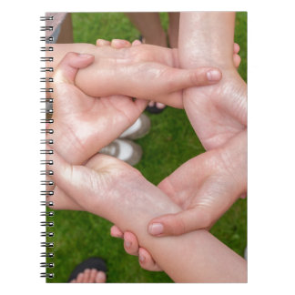 Arms with hands of girls holding each other notebook