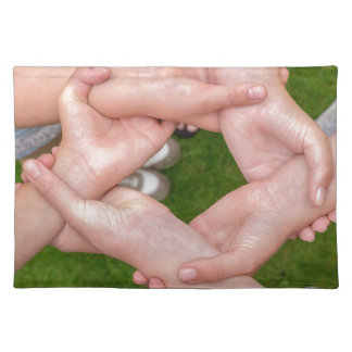 Arms with hands of girls holding each other placemats