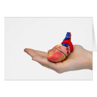 Artificial human heart model on hand card
