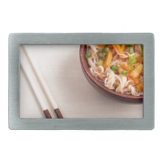 Asian dish of rice noodle in a small wooden bowl belt buckles