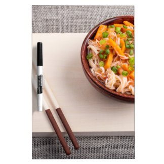 Asian dish of rice noodle in a small wooden bowl dry erase whiteboard