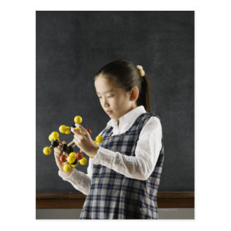 Asian girl looking at molecule model postcard