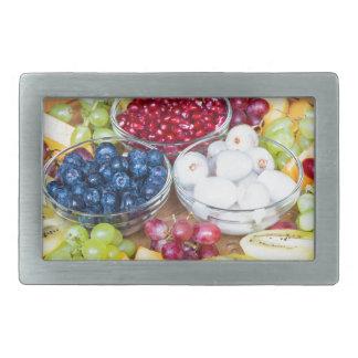 Assortment fresh summer fruit on glass scale belt buckle