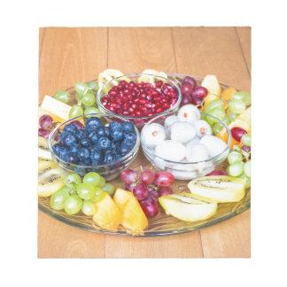 Assortment fresh summer fruit on glass scale notepads