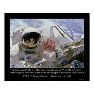 """Astronaut Dale A. Gardner holds up """"For Sale"""" sign"""