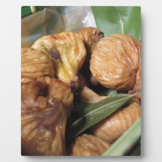Autumn fruits . Closeup of dried figs with leaves Plaque