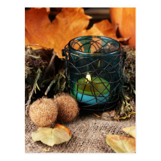 Autumnal composition with candle and leaves postcard