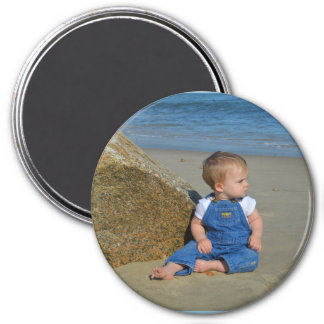 Baby by the ocean pondering. magnet