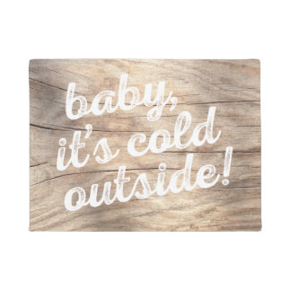 baby, it's cold outside! on light wood background doormat