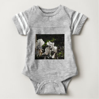 Backlits white cyclamen flowers on dark background baby bodysuit