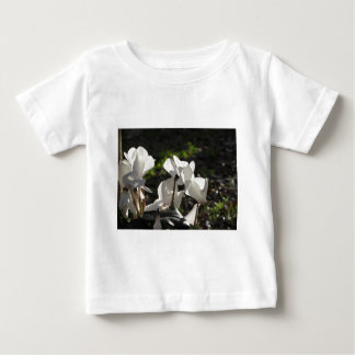 Backlits white cyclamen flowers on dark background baby T-Shirt