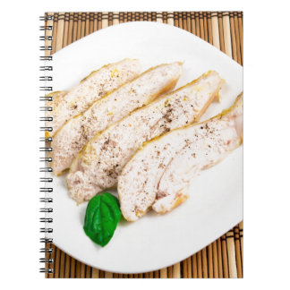 Baked chicken breast sliced on a white plate spiral notebook