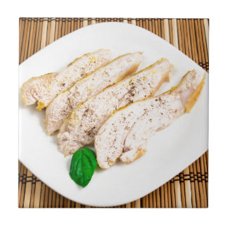 Baked chicken breast sliced on a white plate tile