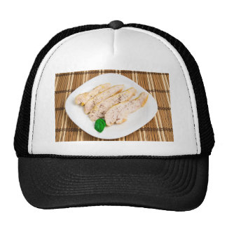 Baked chicken breast sliced on a white plate trucker hat