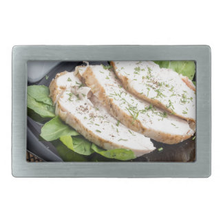 Baked slices of chicken meat on a black plate rectangular belt buckle