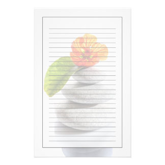 Balanced stones and red flower stationery paper