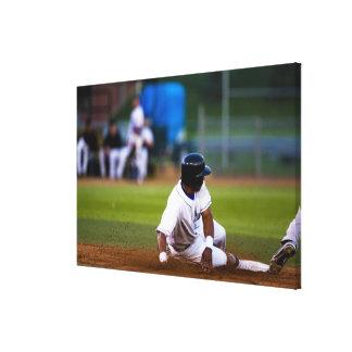 Baseball player sliding onto a base canvas prints