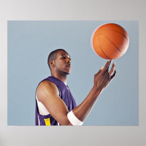 Basketball player balancing ball on one finger poster