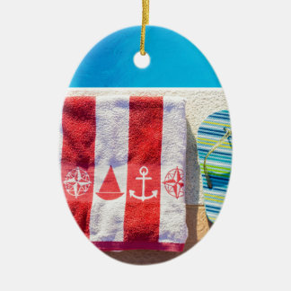 Bathing slippers and bath towel at swimming pool ceramic oval ornament