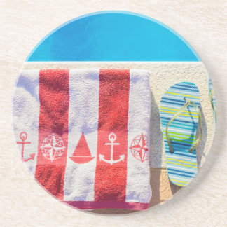 Bathing slippers and bath towel at swimming pool coasters