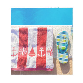 Bathing slippers and bath towel at swimming pool notepad