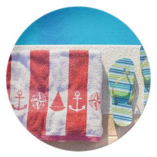 Bathing slippers and bath towel at swimming pool plate