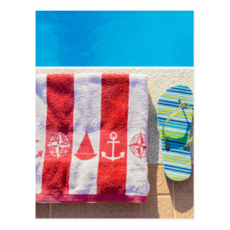 Bathing slippers and bath towel at swimming pool postcard