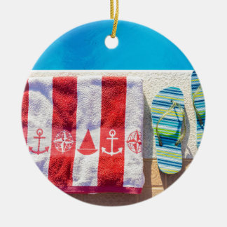 Bathing slippers and bath towel at swimming pool round ceramic ornament