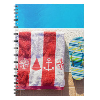 Bathing slippers and bath towel at swimming pool spiral notebook
