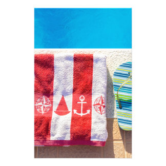 Bathing slippers and bath towel at swimming pool stationery