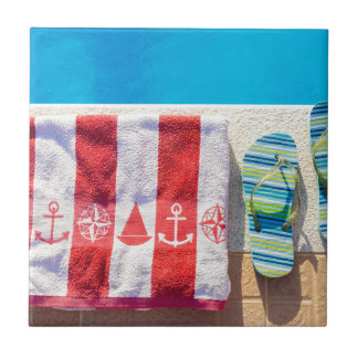 Bathing slippers and bath towel at swimming pool tiles