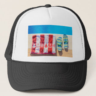 Bathing slippers and bath towel at swimming pool trucker hat