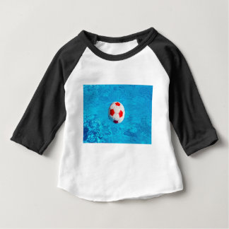 Beach ball floating  in blue swimming pool baby T-Shirt