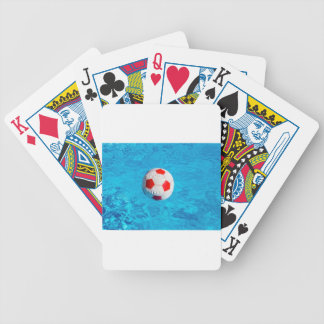 Beach ball floating  in blue swimming pool bicycle playing cards