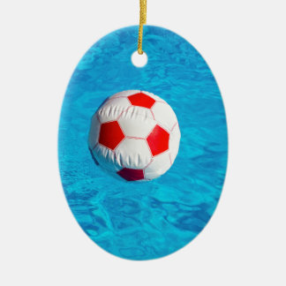 Beach ball floating  in blue swimming pool ceramic oval ornament