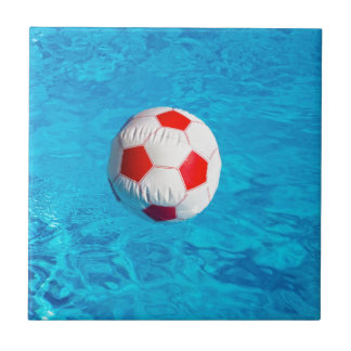 Beach ball floating  in blue swimming pool ceramic tiles