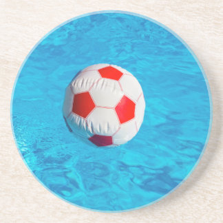 Beach ball floating  in blue swimming pool coaster