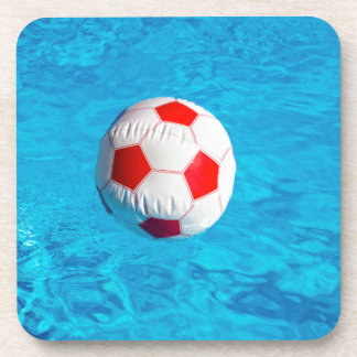 Beach ball floating  in blue swimming pool drink coasters